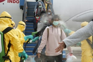 Batam, Indonesia: officials in full protective gear disinfect Indonesian students as they disembark at Hang Nadim international airport. The students had been evacuated from Wuhan in China during the coronavirus outbreak
