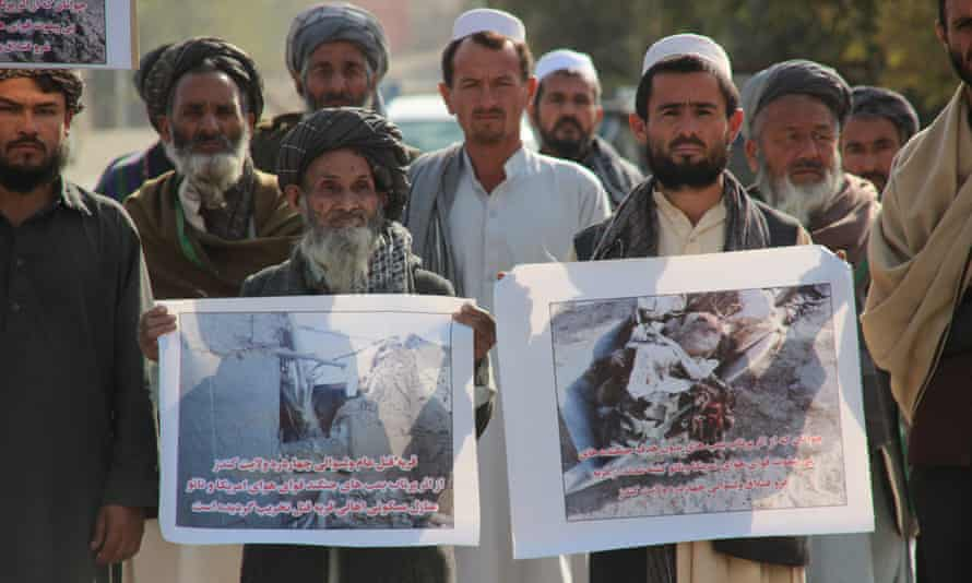 Afghan civilians hold pictures of the victims and damage caused by US airstrikes, during a protest in Kunduz, Afghanistan