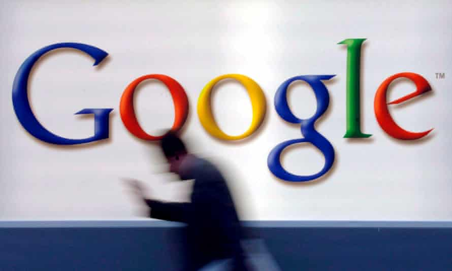 A man passes by a Google logo