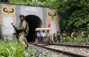 Agartala, India Indian paramilitary stand alert as railway officials ride on a buggy in the Baramura hills during a security search ahead of India's Independence Day celebrations