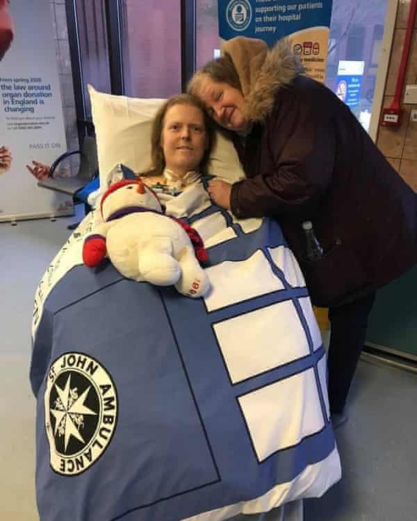 Woman with her arm around man covered by St John Ambulance blanket with cuddly toy