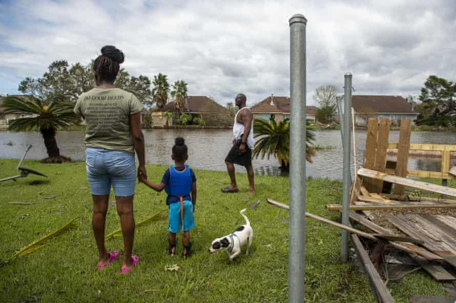 Wearing a life jacket for the walk through their flooded neighborhood, Royal Williams, four, holds the hand of his mother, Tarnequa, as they and Torris Williams, her father, along with their dog Marshall, survey the damage to their backyard in LaPlace, near New Orleans.