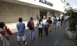 People line up at a supermarket to make purchases amid the coronavirus pandemic, in Panama City, Panama, 23 March 2020.