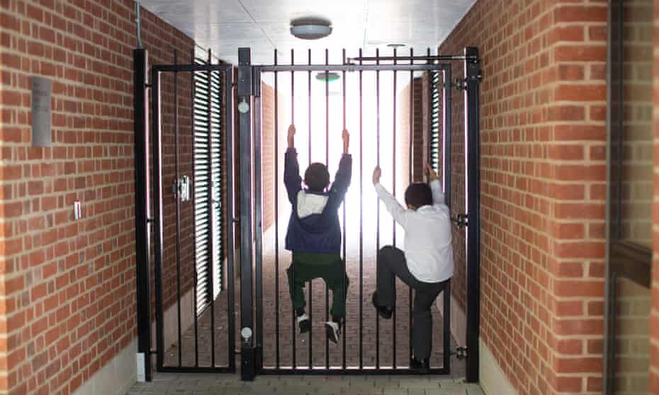 Children on the social housing side of Westbourne Place climb on the gate that prevents access to the development's communal gardens.