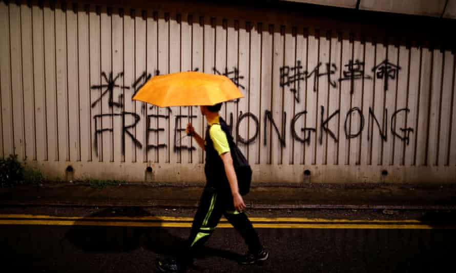 A man walks past a graffiti during a march to demand democracy and political reforms in Hong Kong
