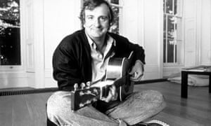 Douglas Adams, sitting cross-legged on the floor, playing a guitar