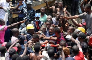 Men carry a boy who was rescued at the site of a building collapse in Lagos, Nigeria, 13 March