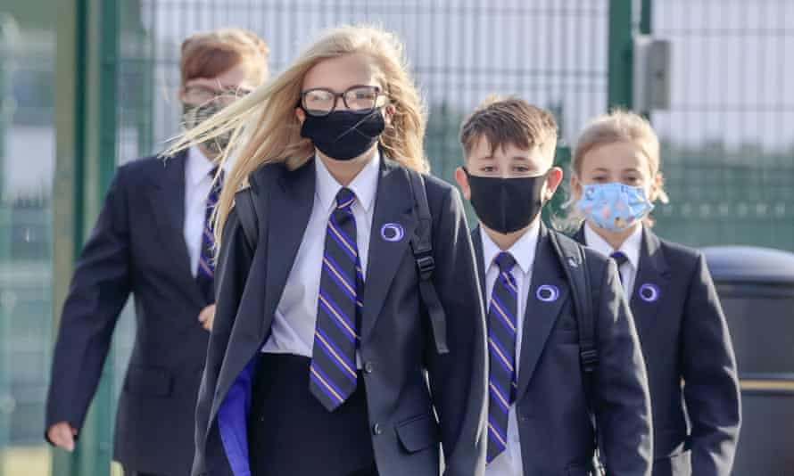 group of pupils in uniform walking towards camera in masks