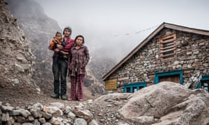 Dawa and Lakpa Sherpa with their daughter outside their guesthouse in the village of Phedi