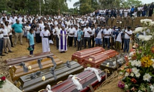 A priest conducts a mass burial for Easter Sunday bomb blast victims in Negombo, Sri Lanka.