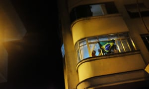 Residents in an apartment display the flag of Brazil as they celebrate after Brazil beat Germany in the final match of the men's football.