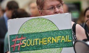 A woman protests against Southern rail services at Victoria station in London.