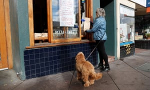 A customer picks up a bag of free pastries from the worker-owned Arizmendi bakery in San Francisco, the morning after the cooperative voted to temporarily shut its doors during day one of the citywide shelter in place order amid the outbreak of coronavirus disease in