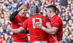 Josh Adams, scorer of Wales's first try against Scotland, and Liam Williams congratulate Jonathan Davies on crossing for the second