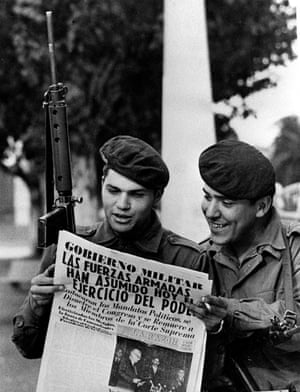 Soldiers read a newspaper in the Buenos Aires Plaza de Mayo after a military coup, 24 March 1976