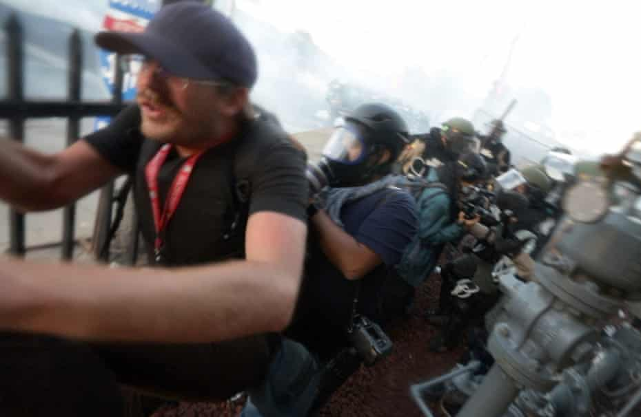 Journalist flee Minnesota State Patrol officers as they spray journalists with pepper spray and fire rubber bullets at them 30 May 2020 outside the 5th Precinct police station in Minneapolis