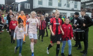 Lewes and Manchester United players walk on to the pitch at The Dripping Pan Stadium.