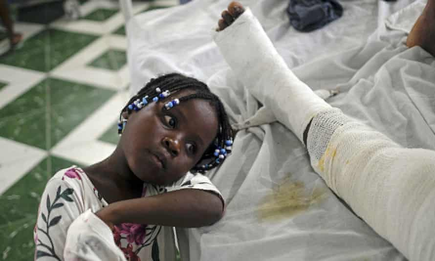 Younaika rests next to her mother, Jertha Ylet, who was injured in the earthquake, in hospital in Haiti