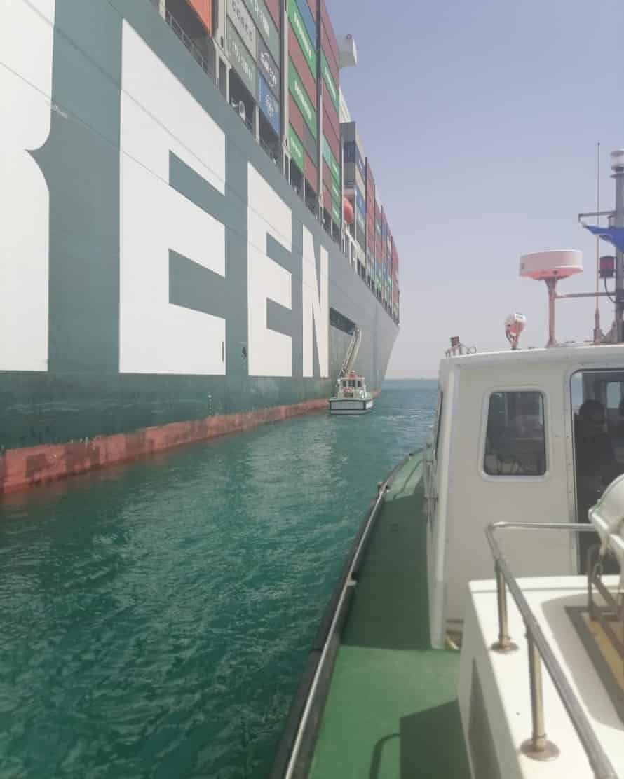 The International Transport Workers' Federation boat pulls up to the Ever Given, showing some of the cargo onboard