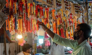 A vendor sprays sanitizer as a preventive measure against the spread of the COVID-19 coronavirus on 'rakhis' (sacred thread) at his shop ahead of the annual Hindu festival 'Raksha Bandhan', in Hyderabad on July 31, 2020. -