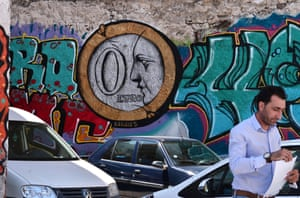 A man walks by a ' 0 Euro' graffiti at a parking lot in Athens on May 25, 2015. Greece warned it has no money to repay the International Monetary Fund on time in June unless a deal is reached with its creditors, in a stark warning that the country could be just days away from defaulting. AFP PHOTO/ Louisa GouliamakiLOUISA GOULIAMAKI/AFP/Getty Images