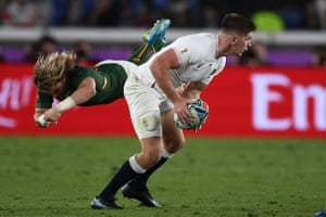 England's centre Owen Farrell (R) holds the ball past South Africa's scrum-half Faf de Klerk during the Japan 2019 Rugby World Cup final match.