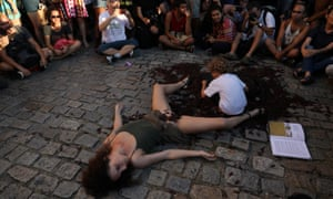A member of the artistic group És Uma Maluca performs while surrounded by fake cockroaches in Rio de Janeiro on Monday.
