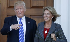 President-elect Donald Trump calls out to the media as he and Betsy DeVos pose for photographs at Trump national golf club in Bedminster, New Jersey.