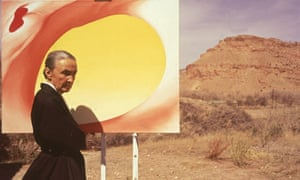 Georgia O'Keefe poses outdoors in Mexico in 1960 with a canvas from her Pelvis Series Red with Yellow.