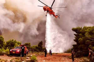 A firefighting helicopter drops water to extinguish flames during a wildfire at the village of Kineta.