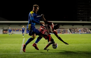 Joe Pigott puts pressure on Doncaster Rovers' Cameron John. Pigott had the distinction of scoring the first goal at the new stadium, smashing a low drive home from 10 yards out after 17 minutes