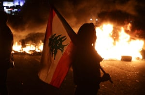 Byblos, Lebanon. An anti-government protester carries a Lebanese flag in front of burning tyres blocking the main highway linking Tripoli to Beirut. Protesters took the streets after President Michel Aoun's televised interview