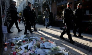 French police officers on patrol in Strasbourg walk past flowers and candles in the Rue des Orfevres in tribute to the two victims of the shooting.