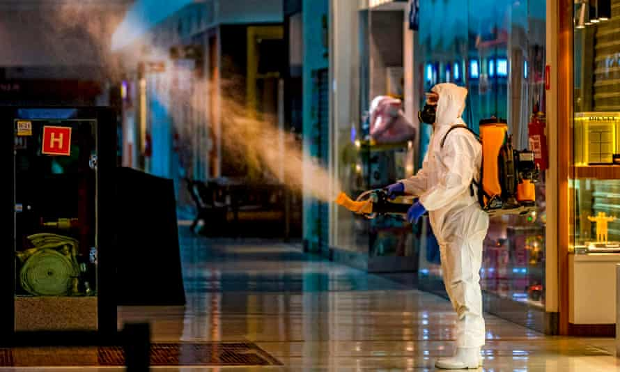 An employee wearing protective gear disinfects a shopping mall in Caxias do Sul, Brazil, on 13 May.
