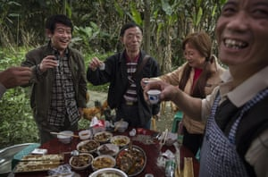 Villagers toast a birthday with wine at a home near the rail line in the former mining town of Bagou
