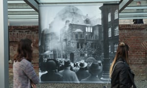 Visitors look at a photo of a synagogue burning in 1938 at a Berlin exhibition related to Kristallnacht