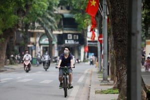 A man wearing a face mask rides a bicycle in Hanoi, Vietnam.