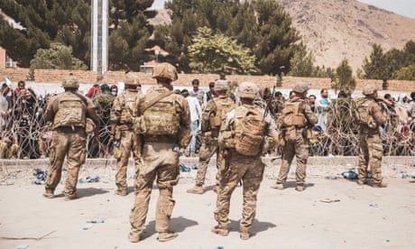 US armed forces personnel assist with security at an evacuation control checkpoint at Hamid Karzai international airport.