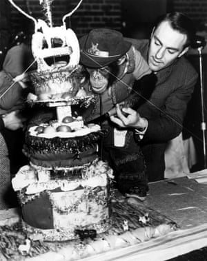 Tottenham Hotspu's Jimmy Greaves helps a young chimpanzee called 'Linda' cut the Christmas cake at a PDSA Animal Party in Ilford in 1964