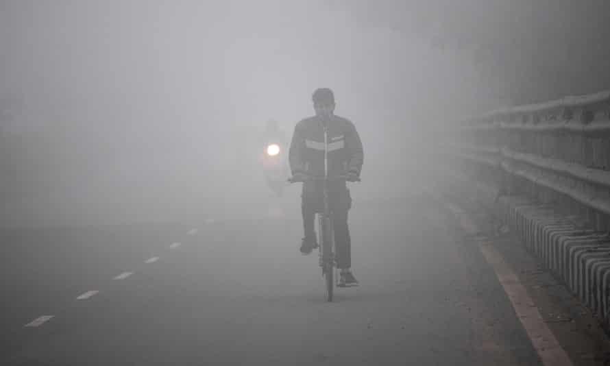 A man rides a bicycle along a street in heavy smog in Delhi.