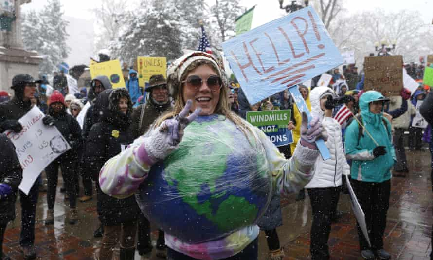 Amy Guerrieri, of Fort Collins, Colorado, wears a home-made model of earth and participates in a climate change awareness march and rally, in Denver.
