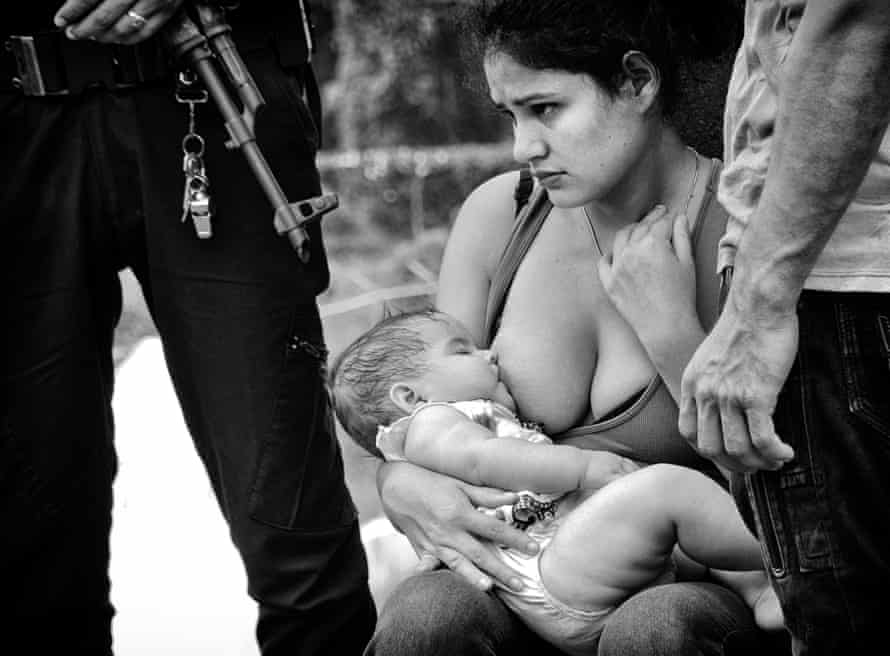 Ariana Elisabeth is five months old and the youngest in the caravan; her parents are escaping life-threatening gang activity in Honduras. Next to them is a Guatemalan board guard.