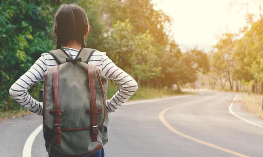 A young girl on the side of a road.