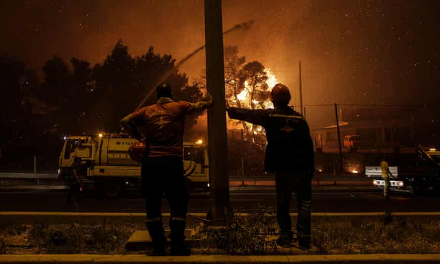 Volunteer firefighters watch as flames approach a highway in Afidnes, near Athens, Greece