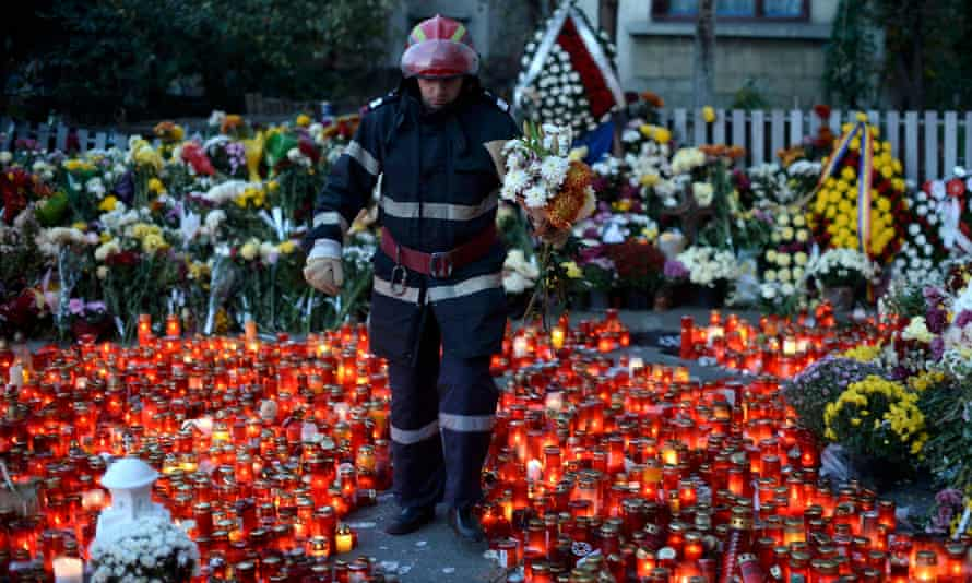 A fireman carries flowers left in memory of the victims of the nightclub fire in Bucharest.