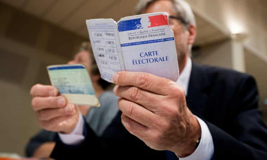 An assessor verifies the identity of a voter in the first round of the French presidential elections in Tulle