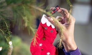 person dressing the christmas tree with a handmade decoration red stocking