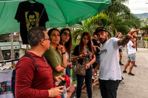 Tour guide Julian Garcia talks to a group of tourists. Together with his friends, Garcia has created a graffiti tour of up to three hours showing visitors the 'cultural wealth of the neighbourhood' for about $10