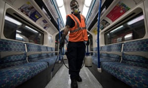 A cleaner disinfects a tube carriage.