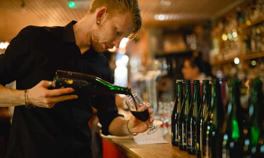 Hipster barman pours dark beer from bottle, North Bar, Leeds